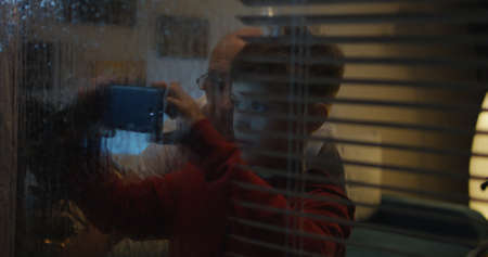 Medium shot of a boy opening blinds to watch the rainfall through the window