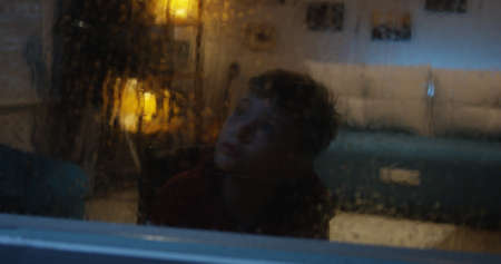 Full shot of a boy in a wheelchair watching rainstorm through the window and moving around