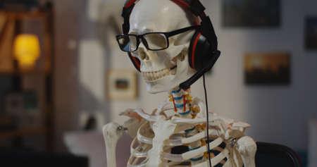 Medium shot of a skeleton wearing headphone dancing while sitting at a computer