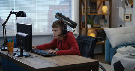 A medium shot of a young disabled boy playing video games while sitting on his wheelchair Imagens