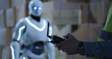 Close up shot of a man controlling a box packing robot with a remote controller 免版税图像