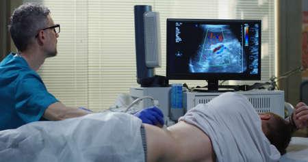 Mittlere Aufnahme eines Arztes, der eine Ultraschalluntersuchung an einem Mann durchführt