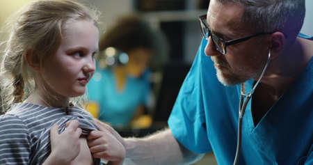 Close-up of a male doctor examining girl with stethoscope