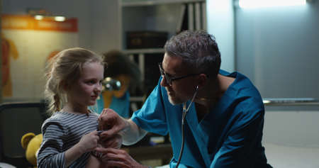 Medium shot of a male doctor examining girl with stethoscope Archivio Fotografico