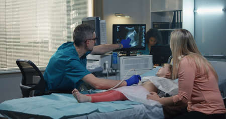 Plano medio de un médico amigable dando cinco a una paciente niña acostada en la cama de un hospital durante el examen de ultrasonido
