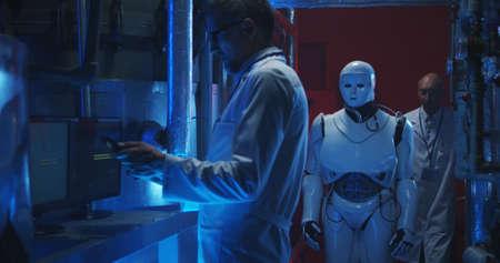 Medium shot of scientists testing humanoid robot