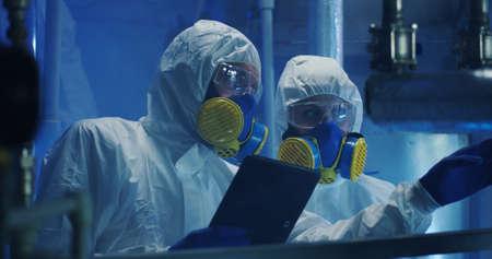 Medium shot of two scientists in hazmat suits conducting maintenance work