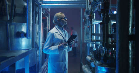 Medium shot of a female scientist checking pressure gauges and other equipment with tablet in her hand 写真素材
