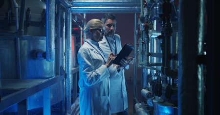 Medium shot of two scientists checking pressure gauge