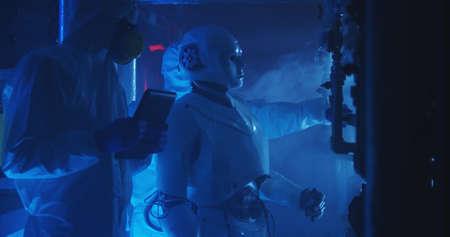 Medium shot of scientists in hazmat suits and a humanoid robot conducting maintenance work 写真素材