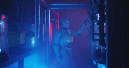 Medium shot of a humanoid robot checking a gauge in a smoke filled lab