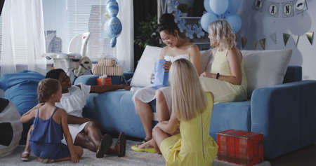 Long shot of friends celebrating young mother with gifts