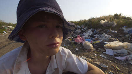 Close up shot of annoyed boy among rubbish in dump