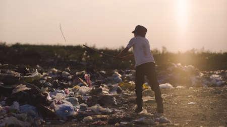 Medium shot of boy kicking dust and hitting garbage in dump