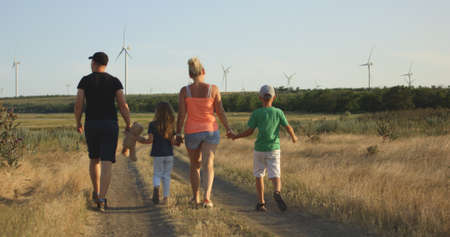 Medium shot of family running over camera in field with windmills in background