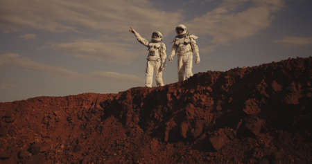 Medium shot of two astronauts pointing and looking away on Mars