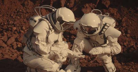 Medium shot of two astronauts collecting rock samples on Mars 免版税图像