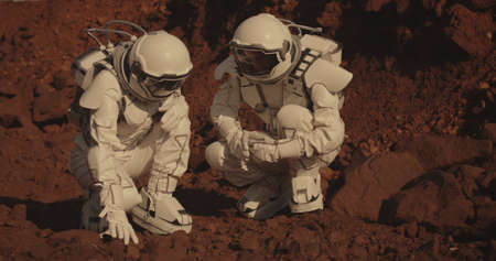Medium shot of two astronauts collecting rock samples on Mars Stock Photo