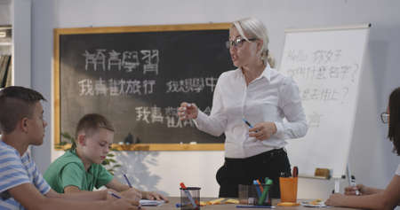 Medium long shot of teacher explaining to pupils in a chinese language class