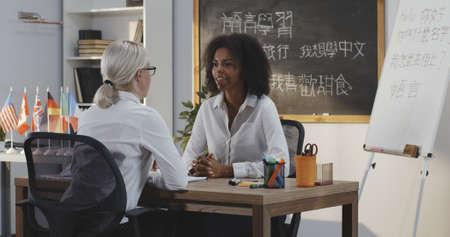 Medium shot of teacher explaining to a student at a language class Stock Photo