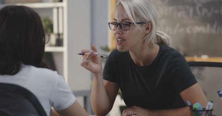 Medium shot of teacher explaining to student in a classroom