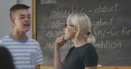 Medium shot of a teacher holding english class