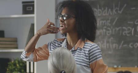 Medium close up of young teacher explaining to a class