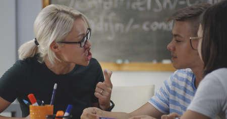 Medium close up of teacher explaining to pupils in a classroom
