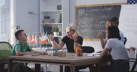 Medium long shot of teacher giving english class white using sticky notes
