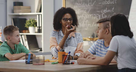 Medium shot of speech therapist explaining to pupils in a classroom