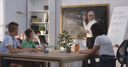 Medium long shot of teacher and pupils in a chinese language class Stock Photo - 128030296
