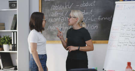 Medium shot of teacher calling out student and giving instructions in a classroom Stock Photo