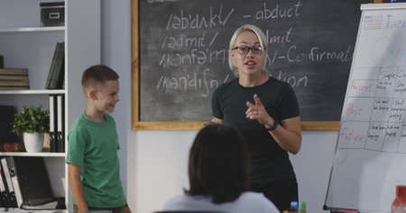 Medium shot of teacher explaining to students and giving instructions in a classroom