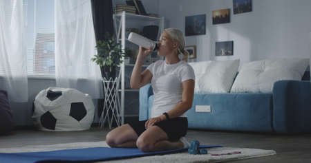 Full shot of a woman hydrating after working out at home Banco de Imagens