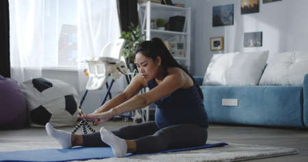 Full shot of a young pregnant woman watching a tutorial video while training at home