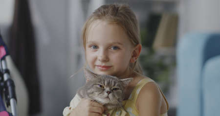 Close up shot of girl holding a cat and looking at camera