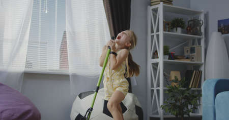 Full shot of girl singing and using mop handle as microphone