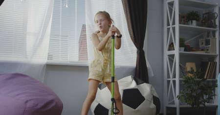 Medium shot of girl singing and using broom handle as microphone