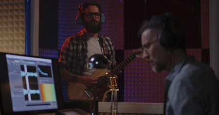 Medium shot of guitarist and sound engineer working in studio