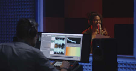 Medium shot of a female actor doing voice over in studio