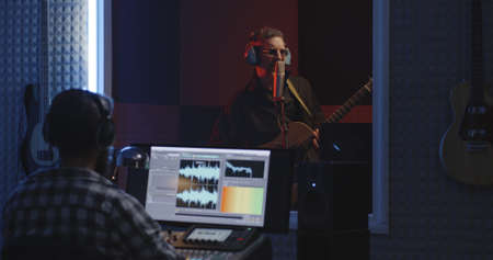 Medium shot of sound engineer recording a guitarist in studio Stock fotó