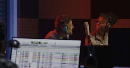 Medium shot of singers completing recording session in a studio