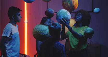 Medium shot of a young female teacher explaining astronomy to students with planet models Stock Photo