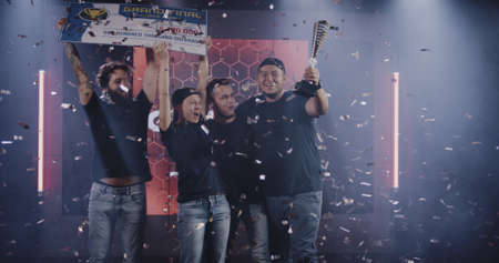 Medium shot of a gaming tournament team holding their prize while celebrating their victory