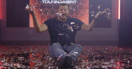 Medium shot of a cheerful young man throwing confetti in the air while looking at camera