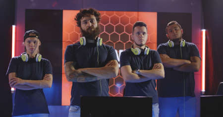Medium shot of a confident gaming team looking at camera with arms crossed
