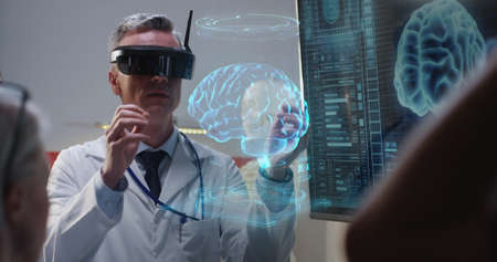 Medium shot of a VR headset wearing doctor explaining to his colleagues while moving holographic 3d brain image Stok Fotoğraf
