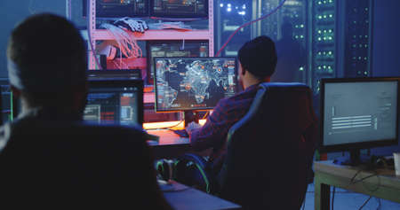 Medium shot of a hacker team working in a dim basement 版權商用圖片