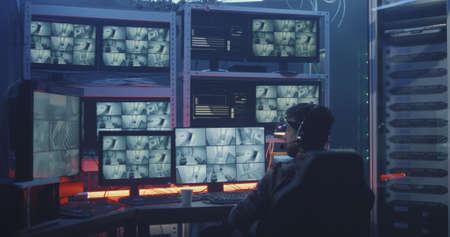 Medium shot of a hacker watching hacked security camera footage