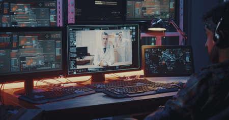 Primer plano medio de un pirata informático que intercepta una videollamada entre dos médicos Foto de archivo